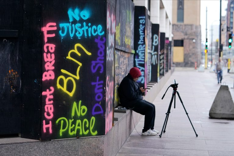 A person videotapes across the street from the Hennepin County Government Center, Thursday, April 8, 2021, in Minneapolis where testimony continues in the trial of former Minneapolis police officer Derek Chauvin. (AP Photo/Jim Mone)