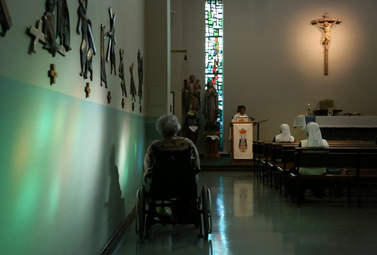 A resident of St. Anne Home sits bathed in sunlight streaming through a stained glass window during morning Mass attended by nuns and residents of the nursing facility in Greensburg, Pa., on Thursday, March 25, 2021. (AP Photo/Jessie Wardarski)