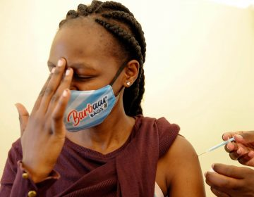 In this April 8, 2021, file photo, a woman at Kenyatta National Hospital in Nairobi, Kenya, receives a dose of AstraZeneca COVID-19 vaccine manufactured by the Serum Institute of India and provided through the global COVAX initiative. (AP Photo/Brian Inganga)