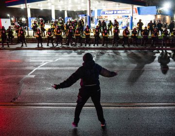 A demonstrator heckles authorities who advanced into a gas station after issuing orders for crowds to disperse during a protest against the police shooting of Daunte Wright, late Monday, April 12, 2021, in Brooklyn Center, Minn. (AP Photo/John Minchillo)
