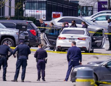 Law enforcement confer at the scene, Friday, April 16, 2021, in Indianapolis, where multiple people were shot at a FedEx Ground facility near the Indianapolis airport. (AP Photo/Michael Conroy)
