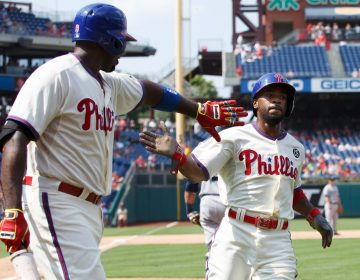 "In this Aug. 20, 2014, file photo, Philadelphia Phillies' Jimmy Rollins, right, celebrates his run with Ryan Howard on a single by Chase Utley during the fifth inning of the team's baseball game against the Seattle Mariners in Philadelphia. When Rollins made his first All-Star team as a rookie with the Phillies 20 years ago, the percentage of Black players in the majors was 13. It's down to 7.6% this year. Rollins pointed to Ken Griffey Jr. and Barry Bonds as popular players who were marketed well when he was growing up. ""But when you start going outside of that select few, the sport itself isn't marketing anyone else in a major way where kids from the inner cities are attracted to it,"