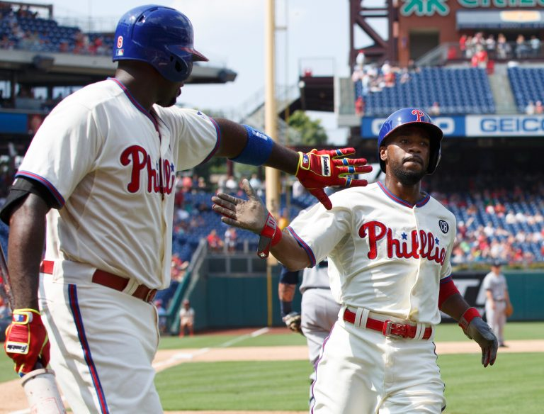 """In this Aug. 20, 2014, file photo, Philadelphia Phillies' Jimmy Rollins, right, celebrates his run with Ryan Howard on a single by Chase Utley during the fifth inning of the team's baseball game against the Seattle Mariners in Philadelphia. When Rollins made his first All-Star team as a rookie with the Phillies 20 years ago, the percentage of Black players in the majors was 13. It's down to 7.6% this year. Rollins pointed to Ken Griffey Jr. and Barry Bonds as popular players who were marketed well when he was growing up. """"But when you start going outside of that select few, the sport itself isn't marketing anyone else in a major way where kids from the inner cities are attracted to it,"""