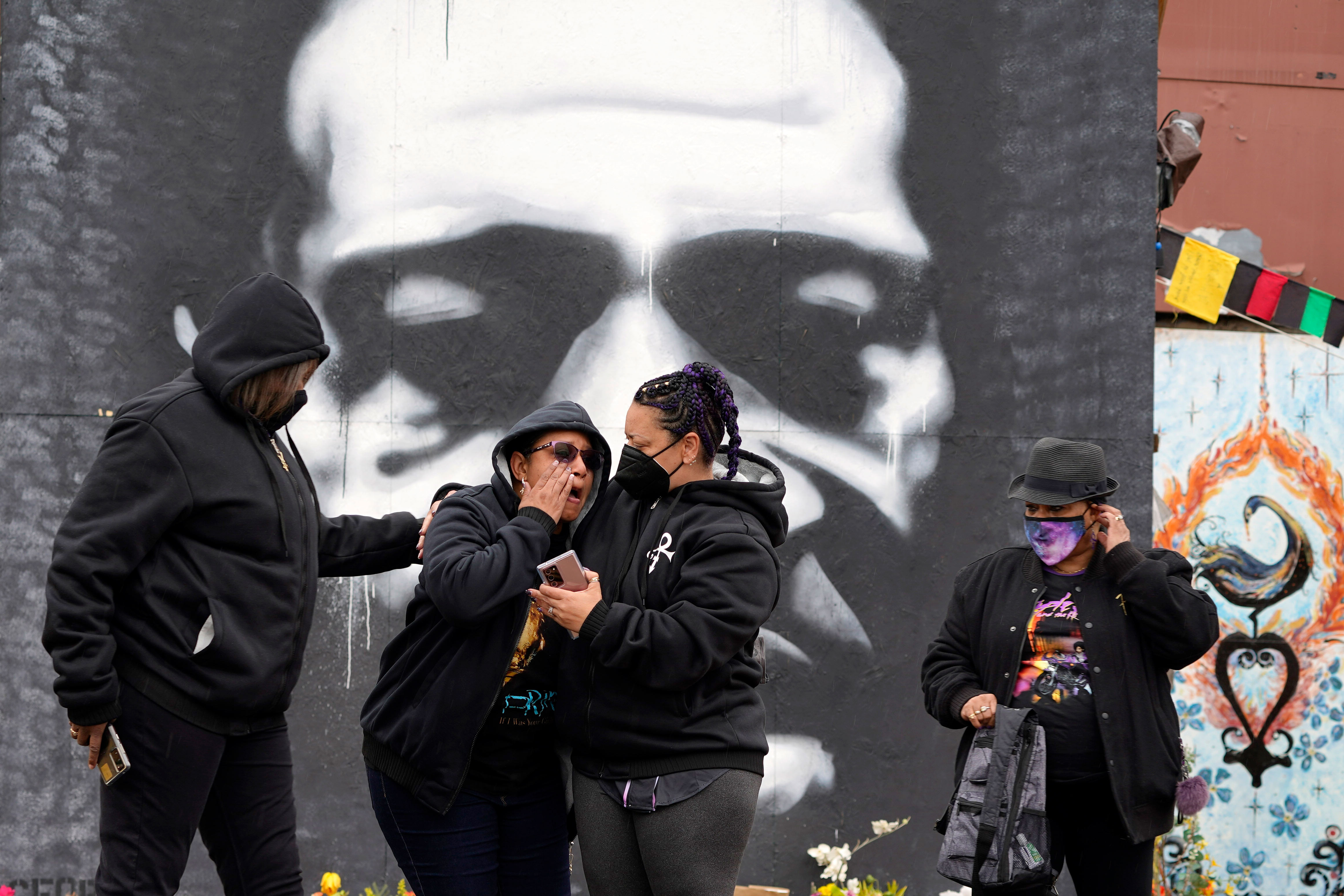 A group of women from Colorado and North Carolina react while paying respects to George Floyd at a mural at George Floyd Square, Friday, April 23, 2021, in Minneapolis. (AP Photo/Julio Cortez)