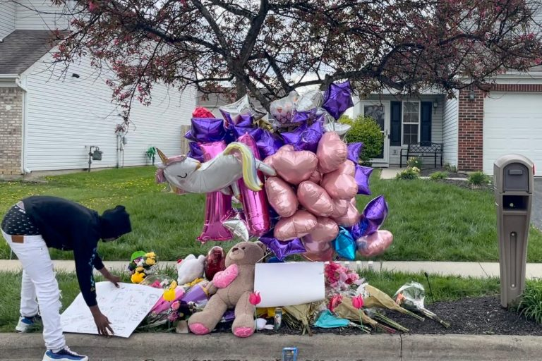A man adjusts a sign near a memorial at the scene in the Columbus, Ohio neighborhood Friday, April 23, 2021 where 16-year-old Ma'Khia Bryant was fatally shot by police as she swung at two other people with a knife on Tuesday, April 20. (AP Photo/Farnoush Amiri)