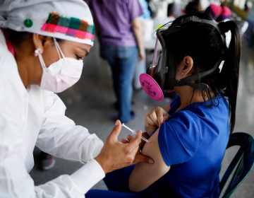 In this April 23, 2021, file photo, a health care worker inoculates Dr. Virma Rivas with the Sputnik V COVID-19 vaccine, as part of a vaccination campaign in Tegucigalpa, Honduras. (AP Photo/Elmer Martinez)