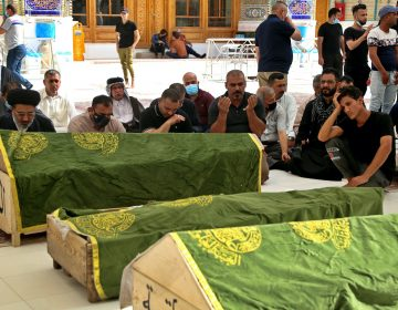 Mourners pray near the coffins of coronavirus patients killed in a hospital fire during their funeral at the Imam Ali shrin