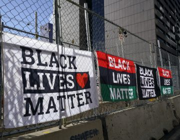 Signs and flags line the fence at the Hennepin County Government Center