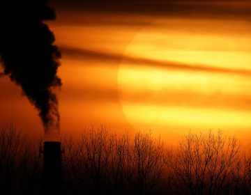 Emissions from a coal-fired power plant are silhouetted against the setting sun