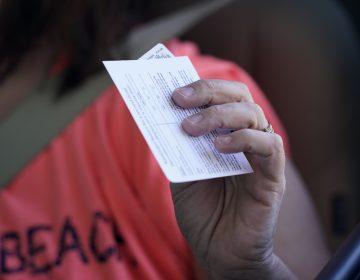Sandy Boeckl holds her inoculation card