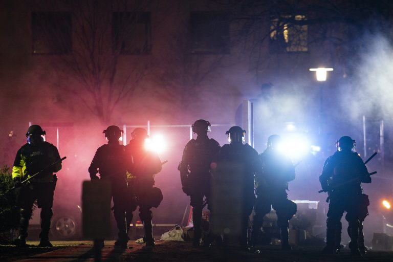 Law enforcement officers clear an area of demonstrators during a protest over Sunday's fatal police shooting of Daunte Wright