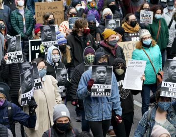People hold signs as they march near the Hennepin County Government Center during a rally in Minneapolis