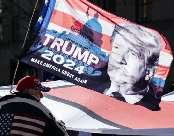 A Trump supporter carries a flag that says