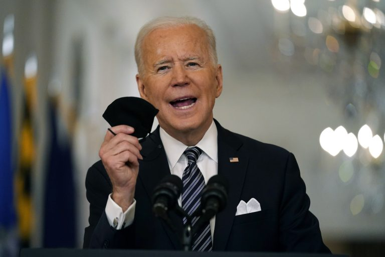 President Joe Biden holds a mask in his hand as he speaks from a podium