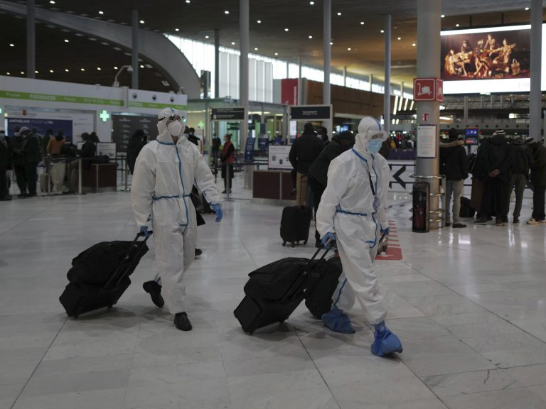 Passengers wearing protective gear arrive to board their plane