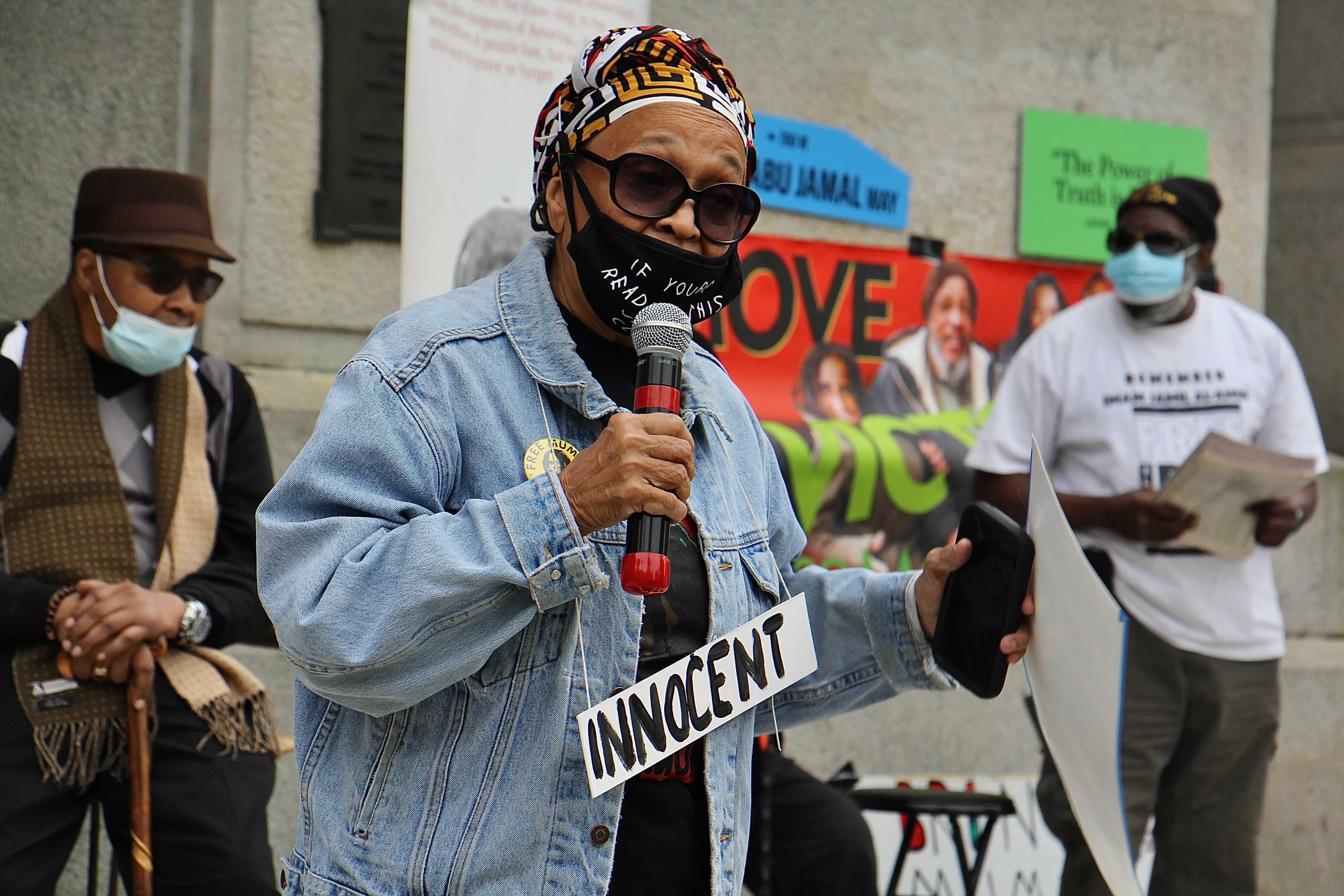 Pam Africa calls for the release of Mumia Abu-Jamal during a rally at City Hall. (Emma Lee/WHYY)