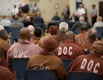 People who are incarcerated in a Pennsylvania prison sit inside while wearing DOC uniforms