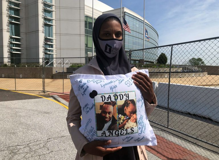 Amanda Spence holds a pillow with photos of her slain husband Lymond Moses and their two children in front of New Castle County police headquarters. (Cris Barrish/WHYY)