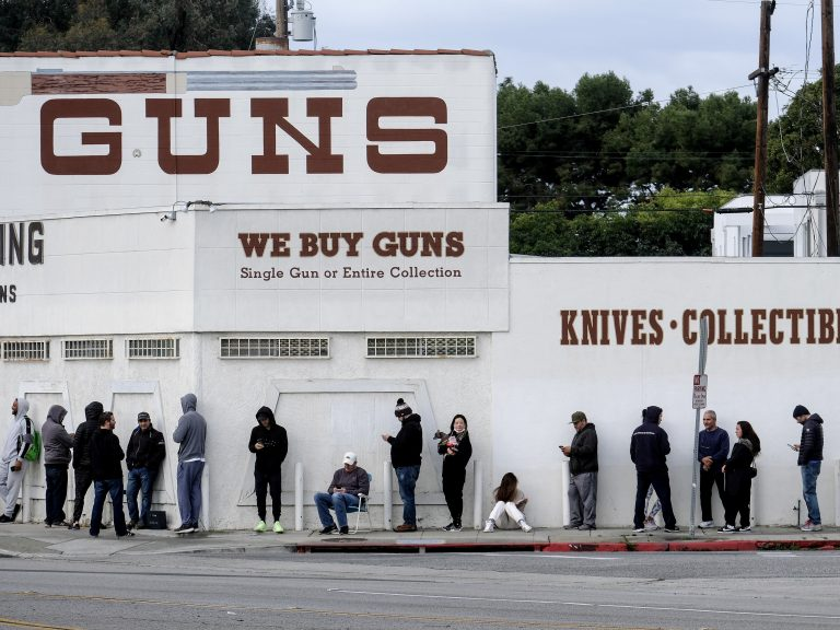 People wait in line to enter a gun store in Culver City
