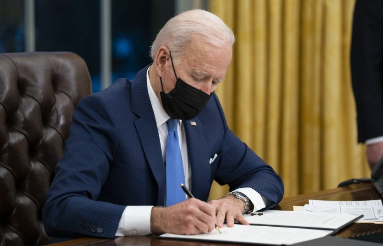 President Biden signs an executive order on immigration in February in the Oval Office. (Evan Vucci/AP)