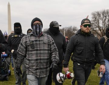 Proud Boy members Joseph Biggs (left) and Ethan Nordean, carrying a megaphone, walk toward the U.S. Capitol on Jan. 6. A federal judge ordered them detained pending trial given the conspiracy charges against them. (Carolyn Kaster/AP)