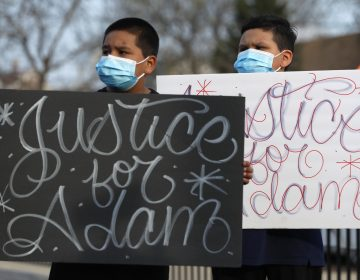 Two boys hold signs at an April 6 news conference, days after a Chicago police officer fatally shot 13-year-old Adam Toledo. (Shafkat Anowar/AP Photo)