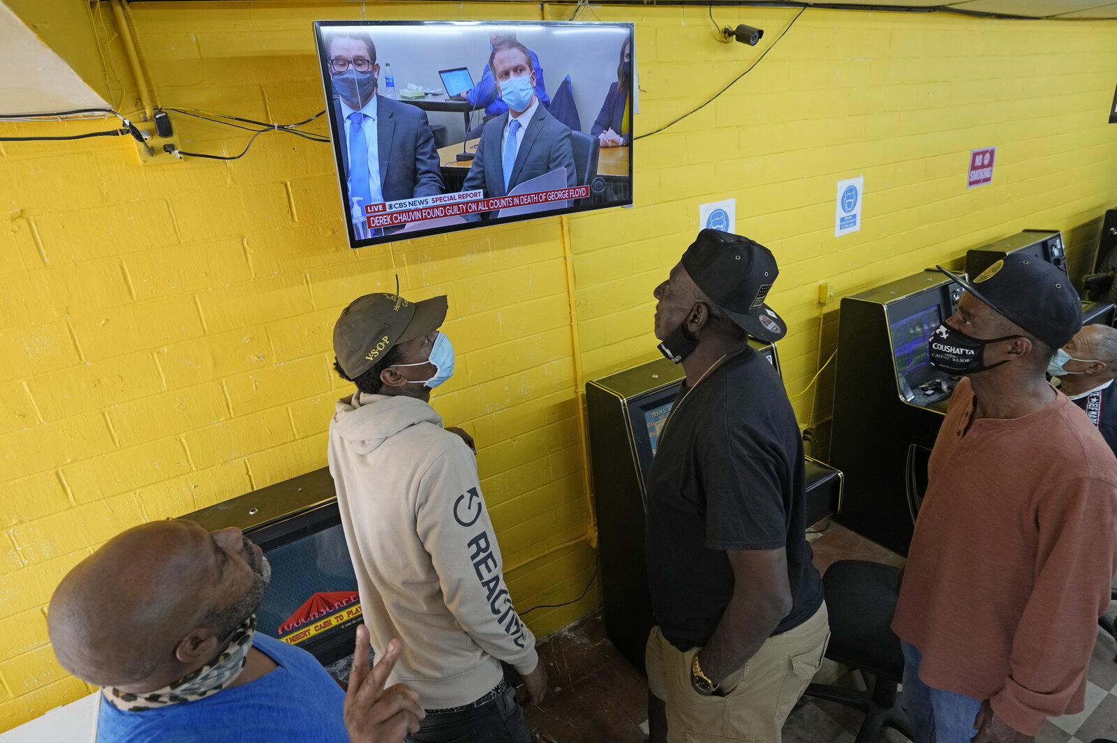 People gather inside a convenience store in the Houston neighborhood where George Floyd grew up, to listen to the verdict in the murder trial of Derek Chauvin