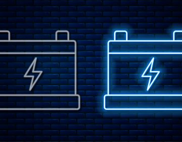 Glowing neon line Car battery icon isolated on brick wall background