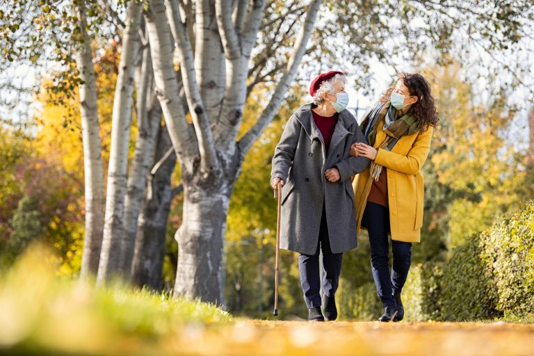 Granddaughter walking with senior woman in park wearing face mask for safety against covid-19