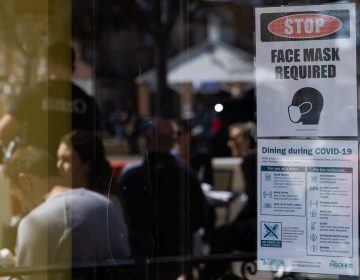 A sign requiring face masks and COVID-19 protocols is displayed at a restaurant in Plymouth, Mich., on March 21. Coronavirus cases in Michigan are skyrocketing after months of steep declines, one sign that a new surge may be starting. (Emily Elconin/Bloomberg via Getty Images)