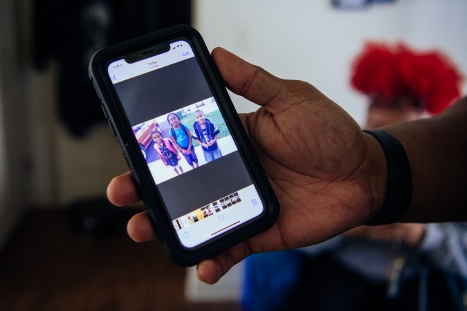 Jonathan showing a photograph of their chidlren on his phone.