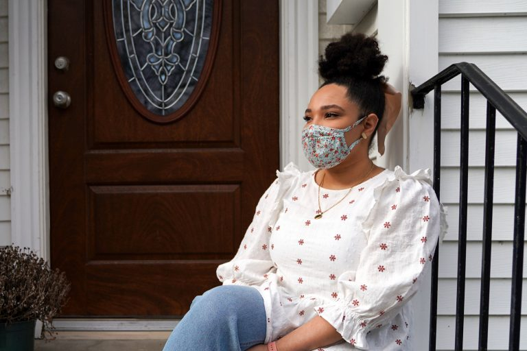 Emily Knowles sits outside her apartment in Watertown, Mass. Knowles has some college credits but no degree and works as a quality assurance analyst at Ovia Health, a Boston-based digital company that serves people who are starting families.