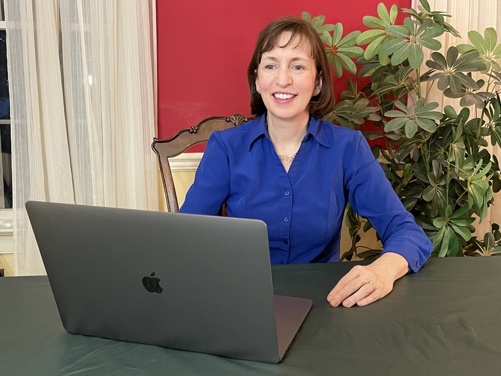 Eileen Kennedy-Moore smiles while sitting behind her laptop
