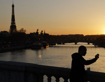 A man takes a picture with mobile phone at the sunset with Eiffel Tower in the background