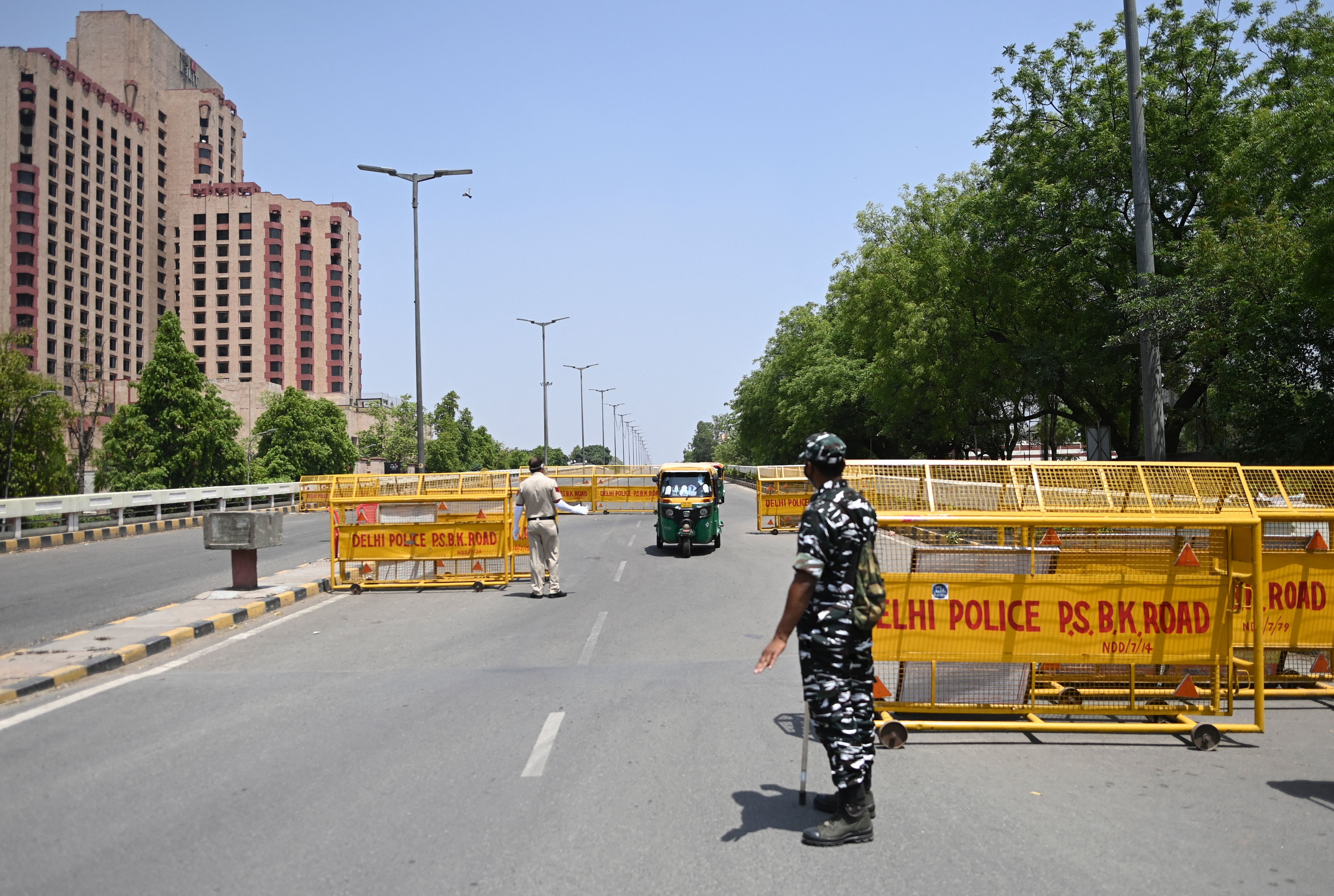 Police stop vehicles April 18 at a New Delhi checkpoint aimed at enforcing a weekend lockdown