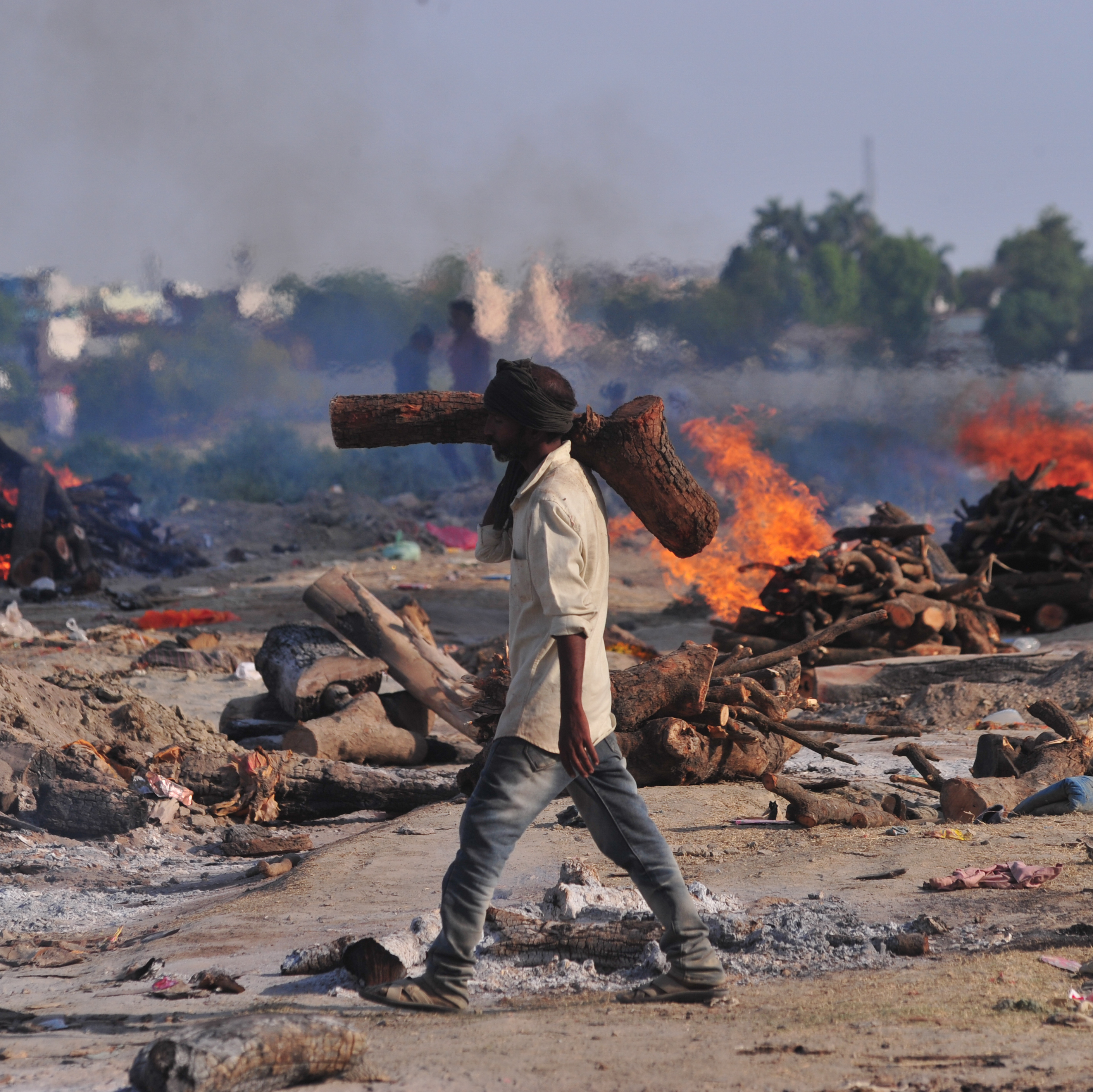 A worker carries wood to a mass cremation site on the banks of the Ganges River in Allahabad