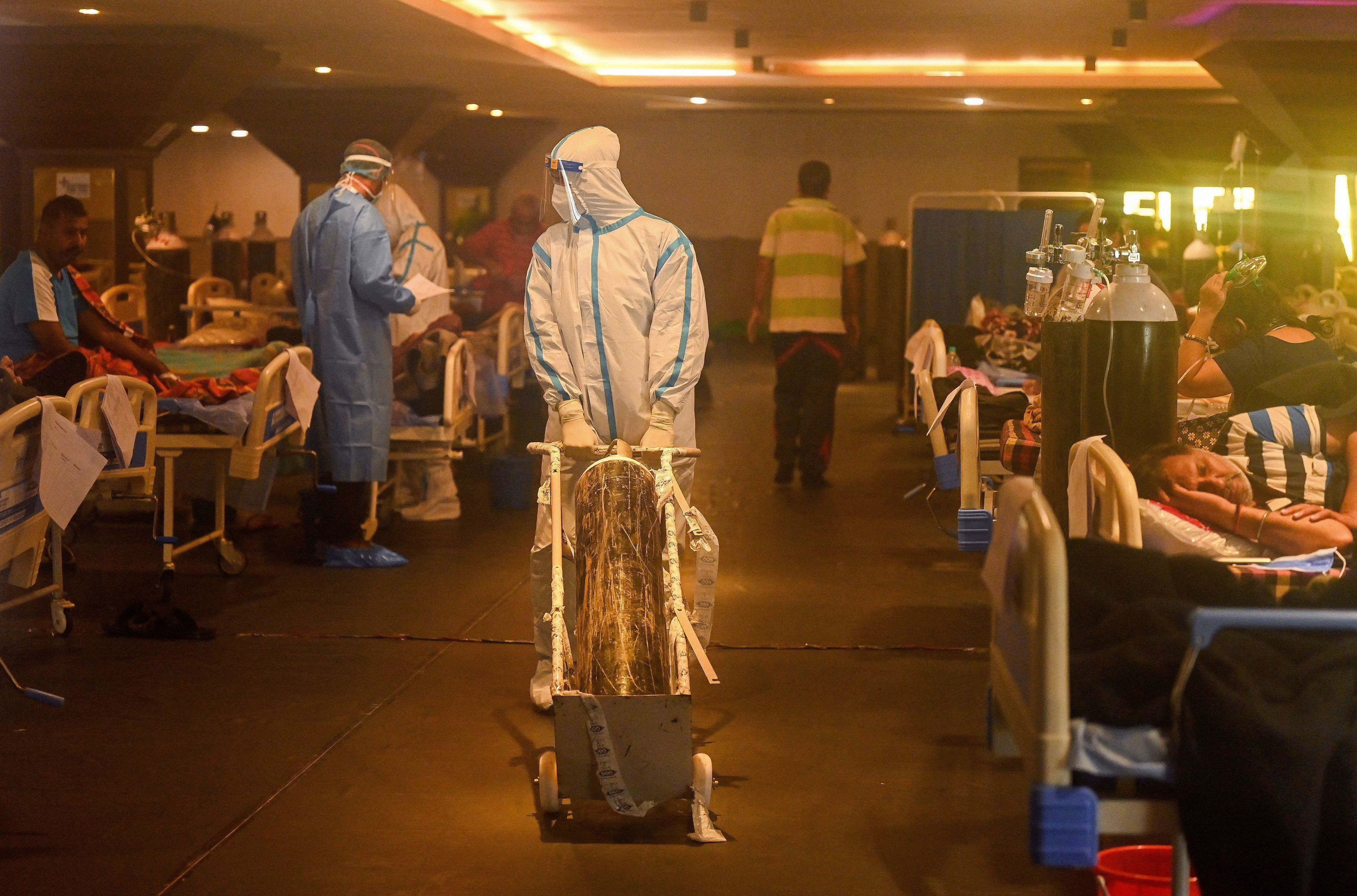 Health workers in protective gear tend to patients Wednesday in a banquet hall temporarily converted into a COVID-19 care center
