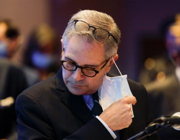 Philadelphia District Attorney Larry Krasner removes his face mask to speak at a news conference