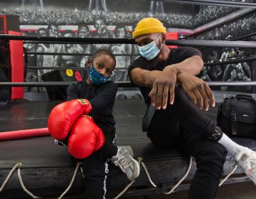 8 year-old Lewis King hangs with Maleek Jackson at his boxing gym in Northern Liberties. (Kimberly Paynter/WHYY)