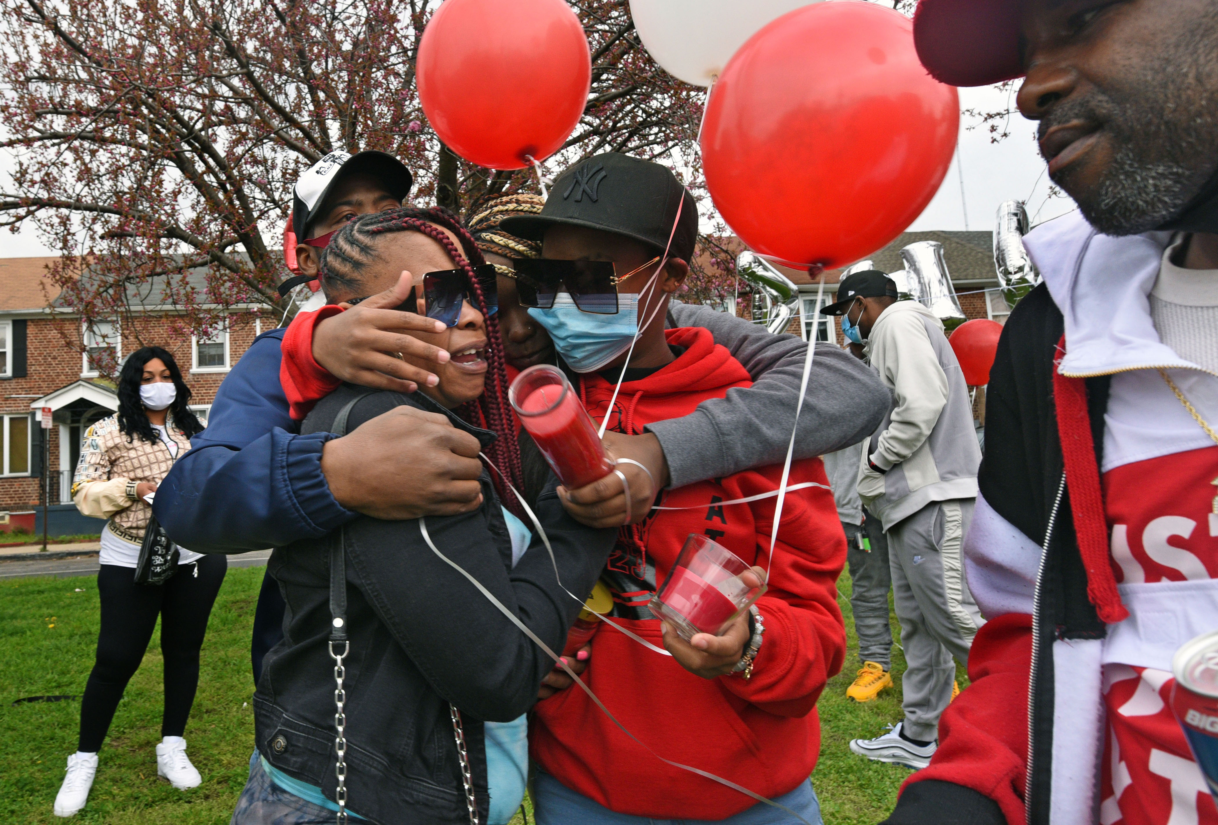 Tomeka Holmes (left) is embraced by family members, including her 15-year-old daughter Siani Custis