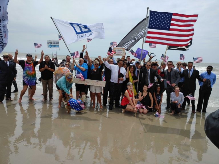 Businesspeople in suits and dresses go into the Atlantic Ocean as part of opening ceremonies in Ocean City, N.J. (Tom MacDonald/WHYY)