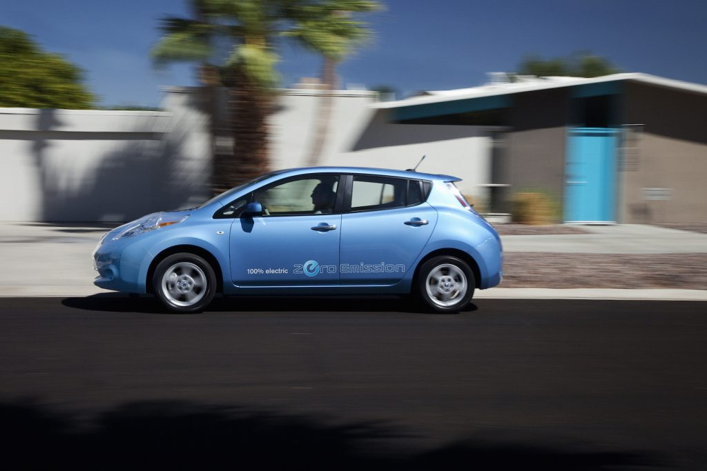 A blue 2012 Nissan Leaf drives on the road.