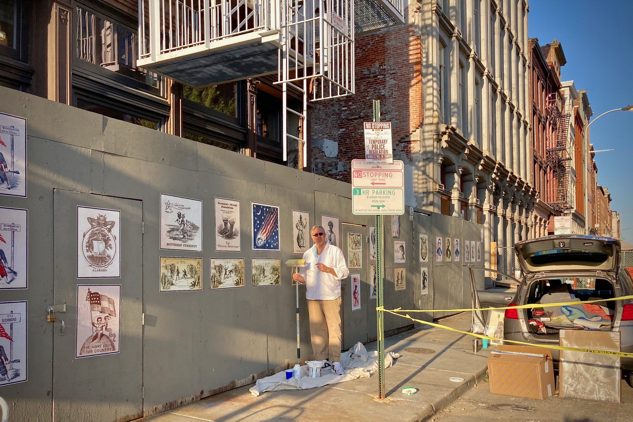 Printmaker Todd Kimmell installs a series of Civil War Era political cartoons on a construction wall at 3rd and Chestnut streets. (Courtesy of Todd Kimmell)