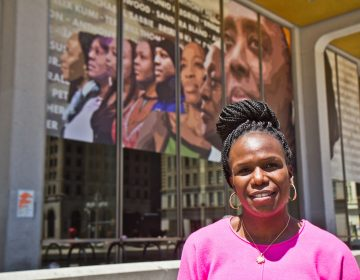 Dr. Ala Stanford, founder of the Black Doctors Consortium, in front of the Crown mural by artist Russell Craig that pays homage to her and other Black women. (Kimberly Paynter/WHYY)