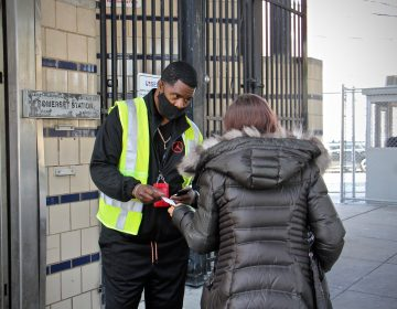 Outreach worker Kenneth Harris engages with a client outside Somerset Station. (Emma Lee/WHYY)