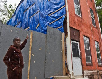 Clarice Brooks points to damage on the side of her home caused by construction on North 7th Street. The house has been owned by her family for 66 years. (Kimberly Paynter/WHYY)