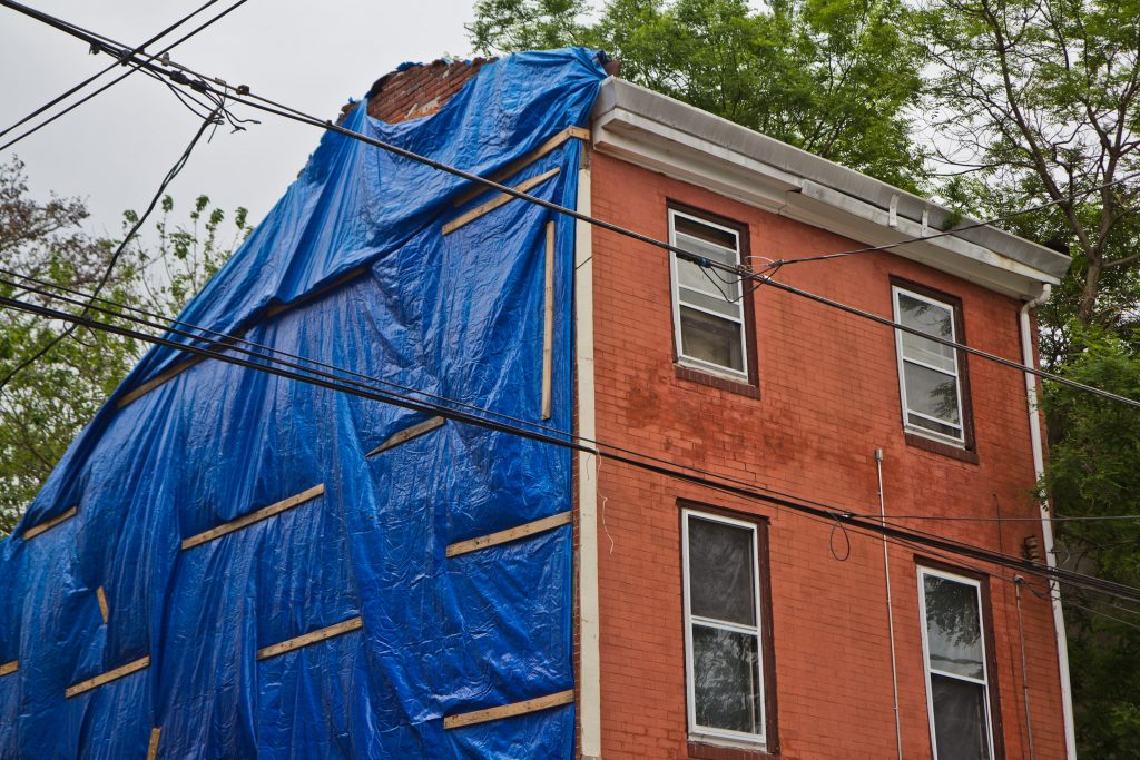 Repair work underway on the side of the Brooks family's home on North 7th Street in Philadelphia. (Kimberly Paynter/WHYY)