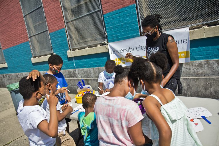 Mitchell Elementary School students color fans at an anti-violence rally and resource fair in Southwest Philadelphia on May 19, 2021. (Kimberly Paynter/WHYY)