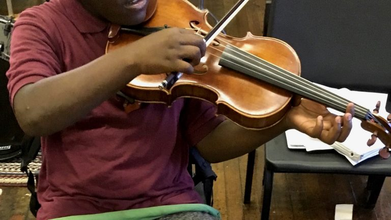 A student practices violin as part of the Philadelphia Arts in Education Partnership. The PAEP has partnered with the DA's office to divert youth offenders into its arts classes. (Courtesey of PAEP)