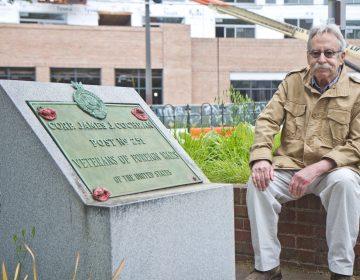 Joel Spivak sits next to a WWI memorial